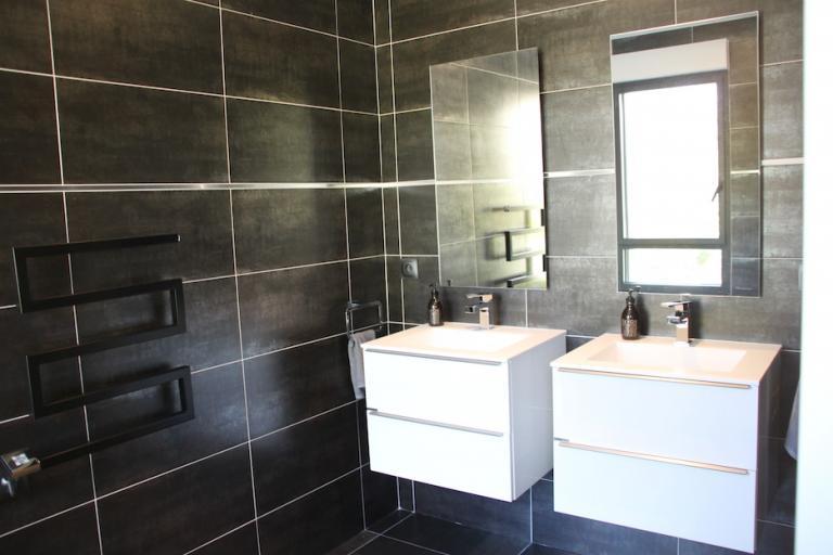Salle de bains avec meubles suspendus et sèche serviette noir